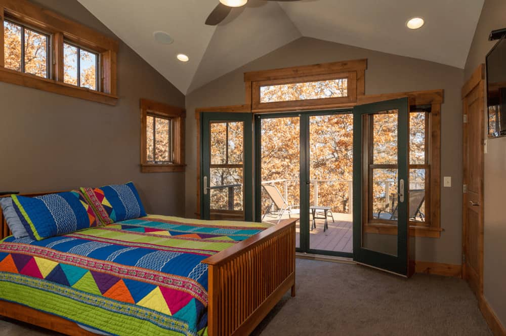 A wooden bed dressed in brightly multi-colored bedding stands out in this brown primary bedroom with carpet flooring and glass double door that leads out to the balcony.
