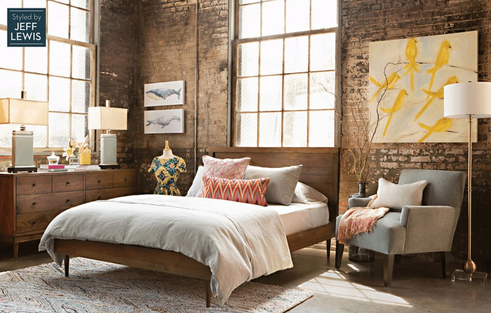 Charming bedroom decorated with lovely table lamps and animal artworks mounted on the rustic brick wall. It has a wooden bed and gray upholstered armchair lighted by a brass floor lamp.