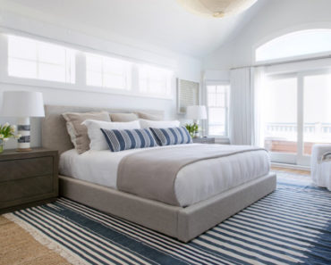 This bedroom plays off a white backdrop against the breezy accents of the carpeted floor, storage cabinet, side lamps and king size bed.