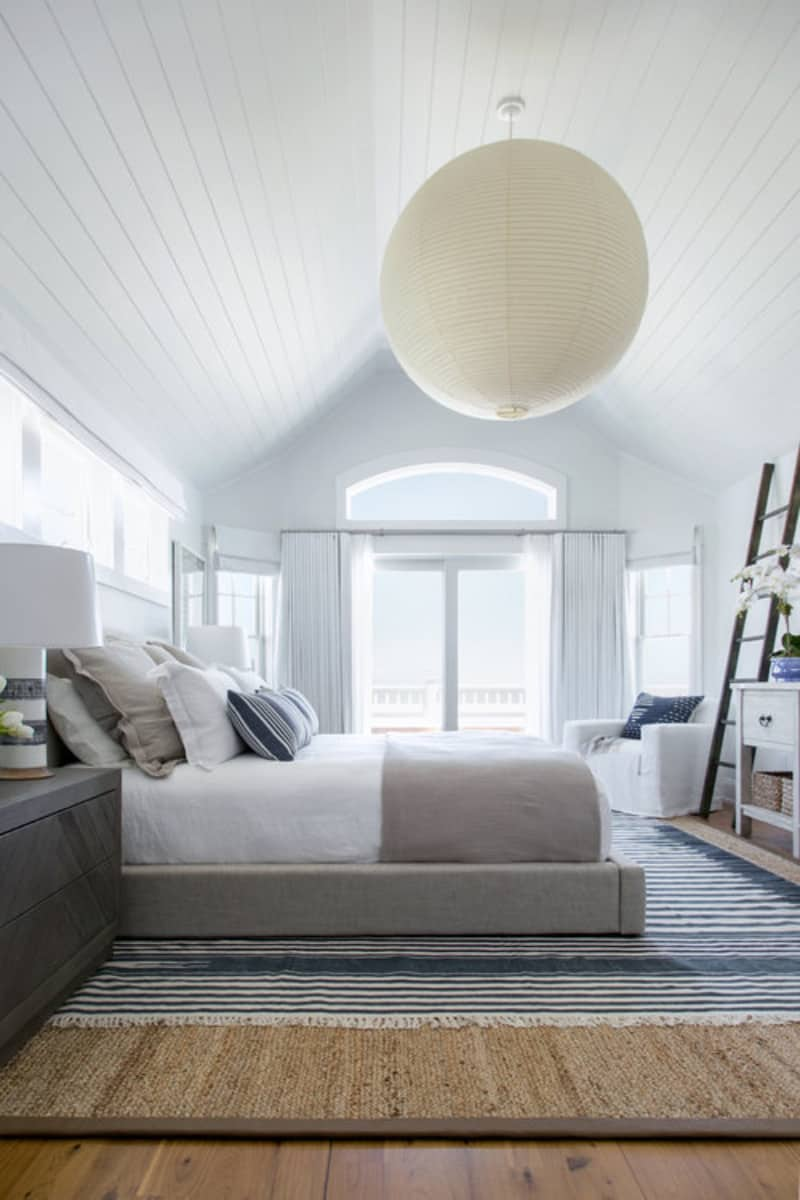 Primary bedroom featuring hardwood flooring topped by a large rug surrounded by white walls and ceiling with a huge pendant lighting.
