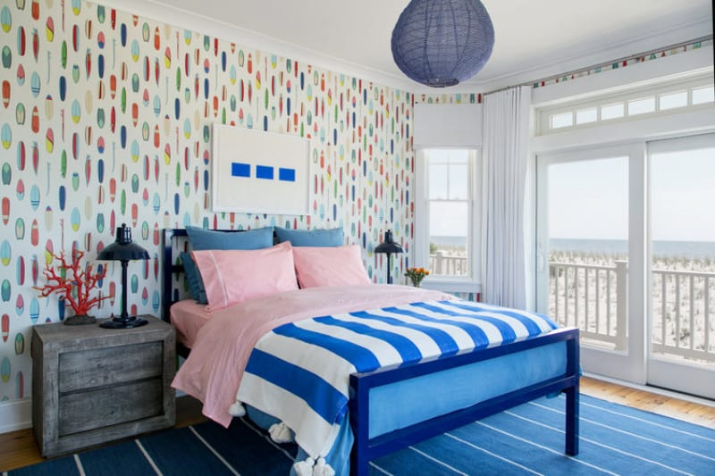 Lively guest bedroom clad in colorful wallpaper features a blue bed on a striped rug illuminated by a round woven pendant. It has hardwood flooring and glass slider that opens to the balcony with a breathtaking beach view.