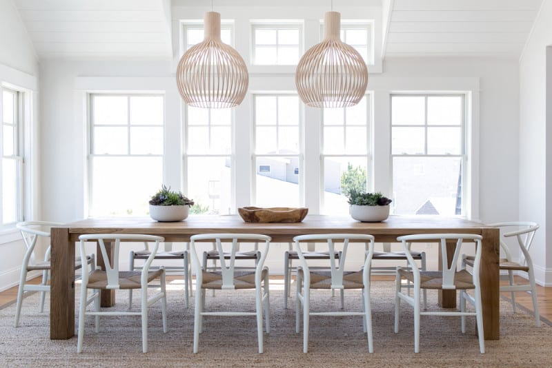 Large wooden dining table set for 10 surrounded by white walls and is lighted by a pair of pendant lights set on the tall ceiling.