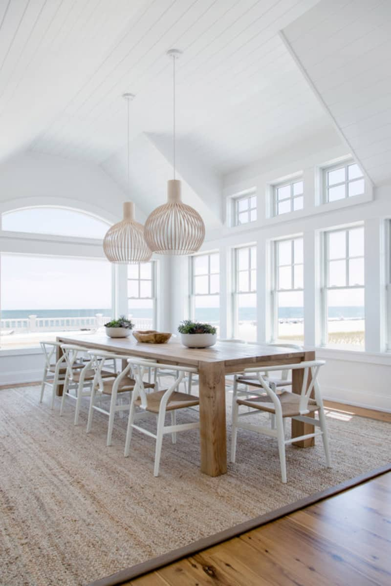 White dining room surrounded with glazed windows that overlook the spectacular beach. It has a vaulted shiplap ceiling and natural hardwood flooring that complements with the dining table.