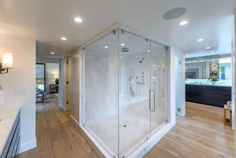This modern bathroom has cool toned hardwood floors and an impressive marble shower stall is a good mix of the old and new. The sinks have soft, accent lighting while the opposite area with marble countertops boasts lantern lights.