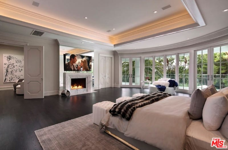 Huge master's bedroom in beige with timeless design featuring full size doors and windows, fireplace and dark transitional wood floors.