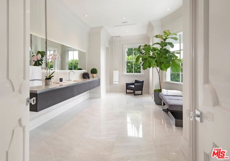 The vanity with extensive cabinets and wide mirror brought a sense of drama to Floyd Mayweather's all-white large bathroom. Further, a huge plant and flowers provide a decorative appeal to it.