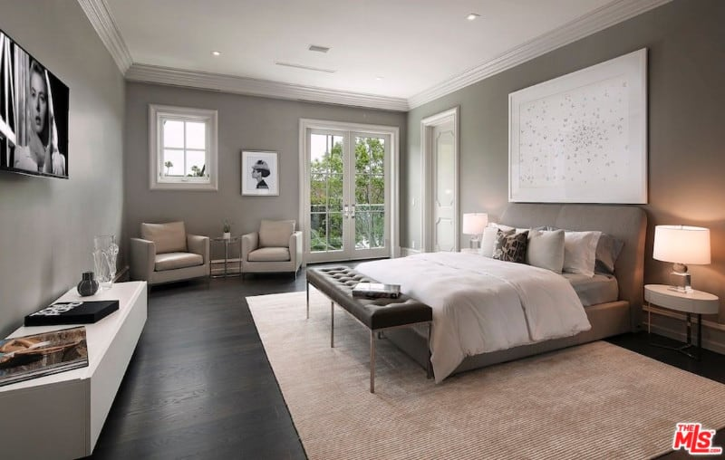 Gray guest bedroom with a sleek bed facing the television that hung above the floating console table and a seating area by the white framed window and French door.