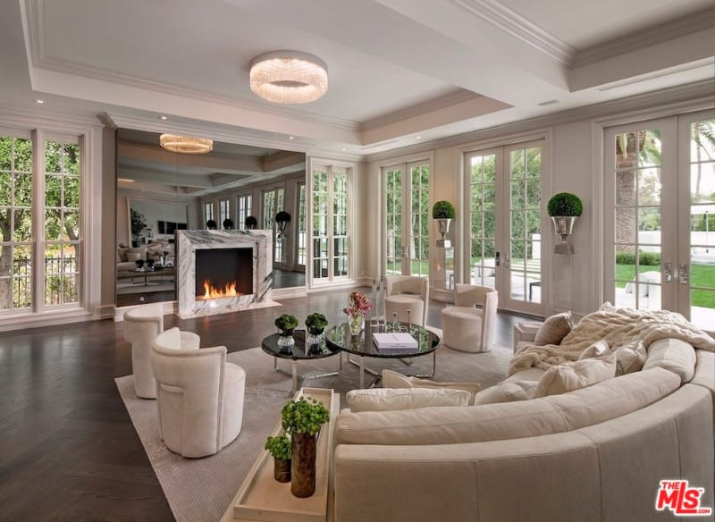 Luxury living room features a curved sofa and round back chairs accompanied with a modular coffee table and marble fireplace fitted on the smoked mirror paneled wall.