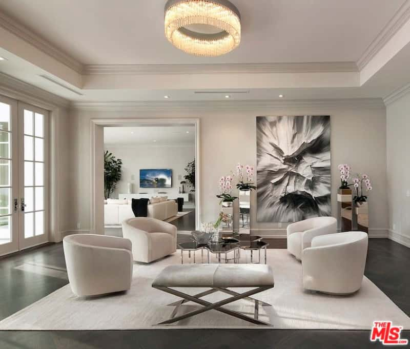 This formal living room offers cozy seats and stylish wall decors, along with dark hardwood floors and a tray ceiling.