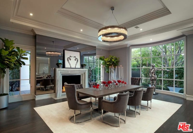 A lavish dining room boasts a luxurious chandelier that hung from a tray ceiling. There's a fireplace fixed on a smoked glass wall facing the wood dining table.