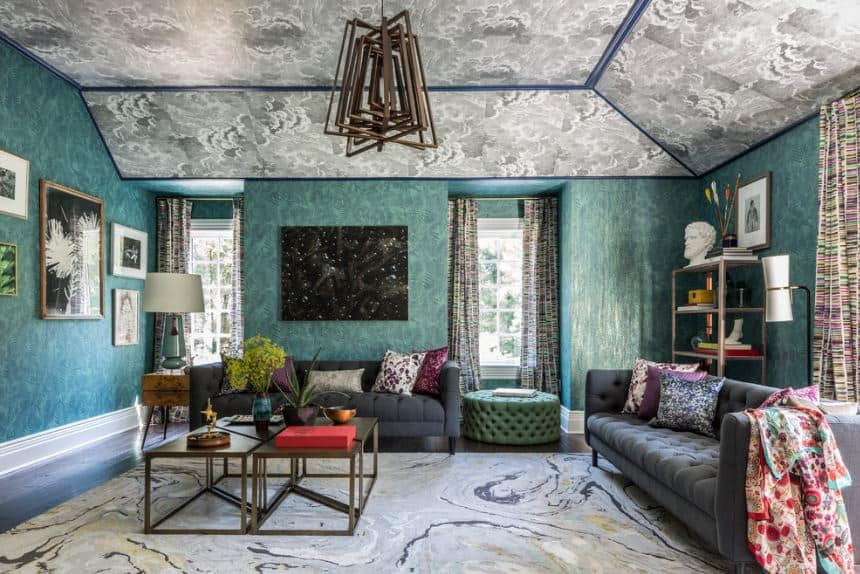 This is an artistic living room with walls of green and a gray ceiling that both have a cloudy design that matches the gray area rug. This is contrasted by dark gray sofas that have floral pillows.