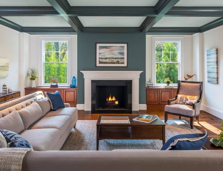 The white tray ceiling's beams are the same color as the green walls that emphasize the fireplace framed with white inlay. This is paired with a light gray L-shaped sofa over a gray woven area rug.