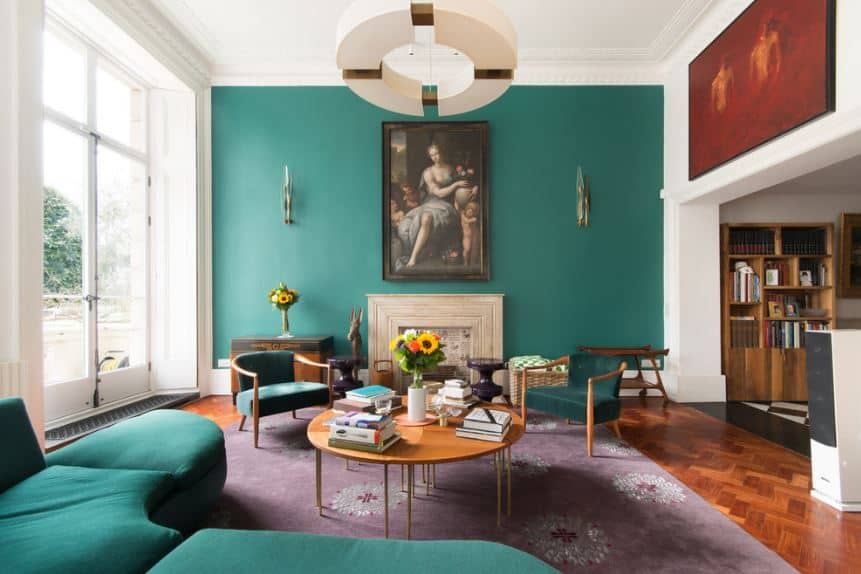 There is a lovely classical painting mounted on the green wall above the beige fireplace that is contrasted with a chic purple area rug that complements the green sofa and armchairs.