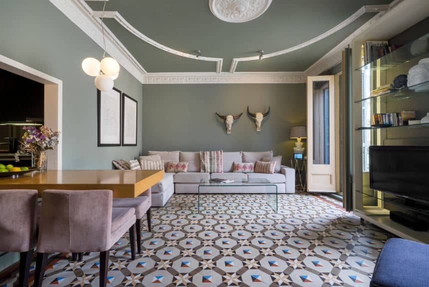 The matte green walls and ceiling are given a complex contrast by the patterned flooring that makes the light gray sofa and glass coffee table stand out.