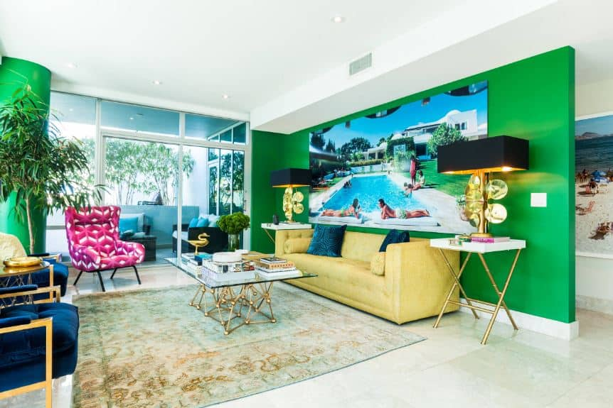 This living room has bold green walls paired with various contrasts of the yellow leather sofa, pink armchair and golden lamps flanking the massive wall-mounted borderless photograph.