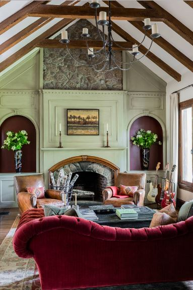 The high cathedral ceiling of this spacious living room has exposed wooden beams that match the colors of the alcove built into the green wall housing the fireplace that faces the red couch and brown leather armchairs.