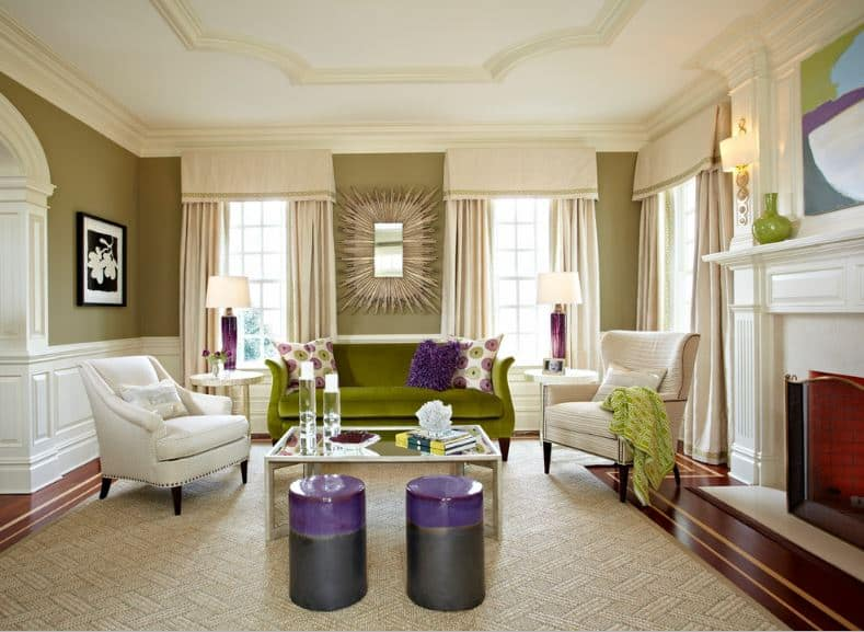 The green walls are dominated by tall curtained windows that illuminate the moss green couch and beige cushioned armchairs blending in with the white wainscoting and white fireplace.