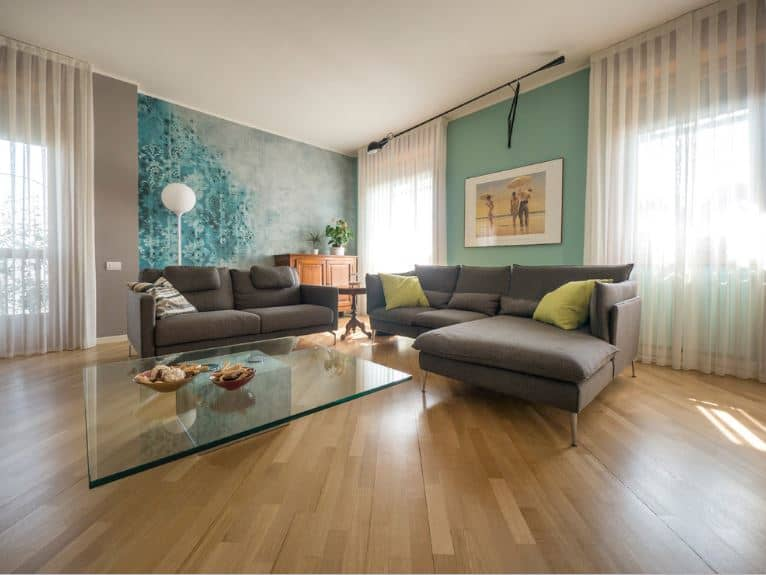 The modern floating glass coffee table is a nice accent to the hardwood flooring the L-shaped gray sofa that contrasts the pastel green walls and curtained windows.