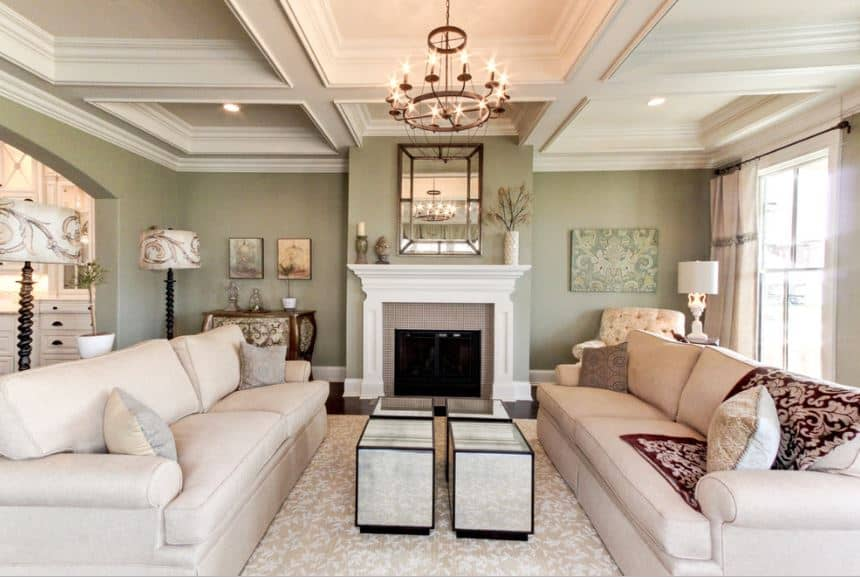 The matte green walls stand out against the uniform beige tray ceiling and a couple of beige couches illuminated by the brilliant warm light of the chandelier.
