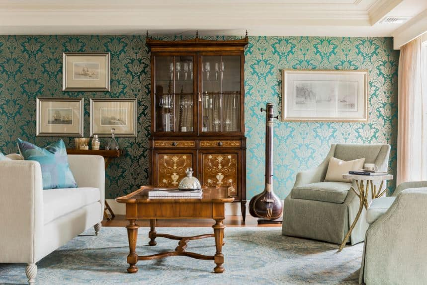 The walls of this bright living room are covered with a patterned green wallpaper that complements the white tray ceiling and white sofa set facing a wooden coffee table.