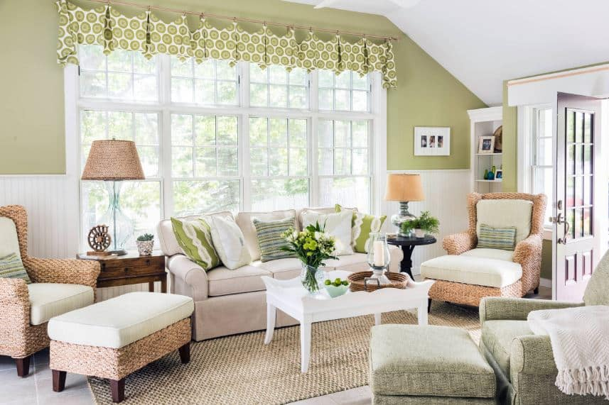 The rustic element of the woven area rug matches the pair of woven wicker armchairs flanking the beige sofa that stands out against the green walls with a massive window.
