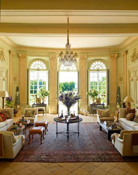 The yellow-green walls are accented with tall beige pillar-like designs that match the pair of beige sofa sets bordering the colorful area rug over the beige floor tiles.