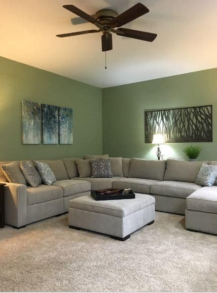 The gray carpeted flooring is a complement to the large gray L-shaped sofa that stands out against the green walls accented with wall-mounted artworks of tree silhouette.