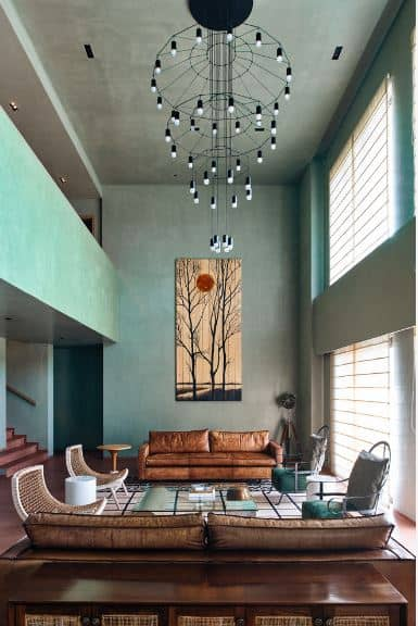 The tall gray ceiling of this spacious living room is complemented by tall green walls that feature a large painting to maximize the vertical space over the leather sofa.