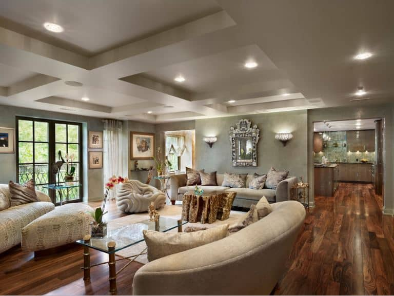 The white tray ceiling is contrasted by hardwood flooring that pairs well with the various beige sofa sets and a tree trunk coffee table. All of these are given a background of green walls that have wall-mounted artworks and lamps.