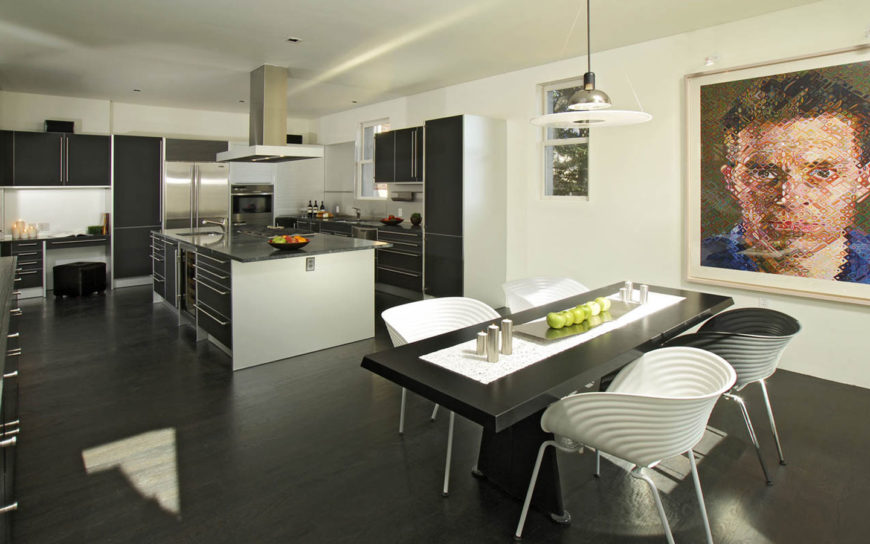 Luxurious black kitchen featuring a sleek vent hood that stands over a kitchen island with built-in cooktop, black cabinet with chrome pulls and stainless steel appliances over a black hardwood flooring.