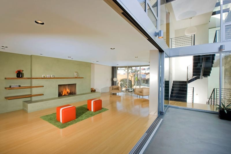 Sleek living room offers a fireplace fixed on the mint green wall lined with floating shelves. It includes a pair of vibrant orange stools that sit on a green rug over the smooth hardwood flooring.