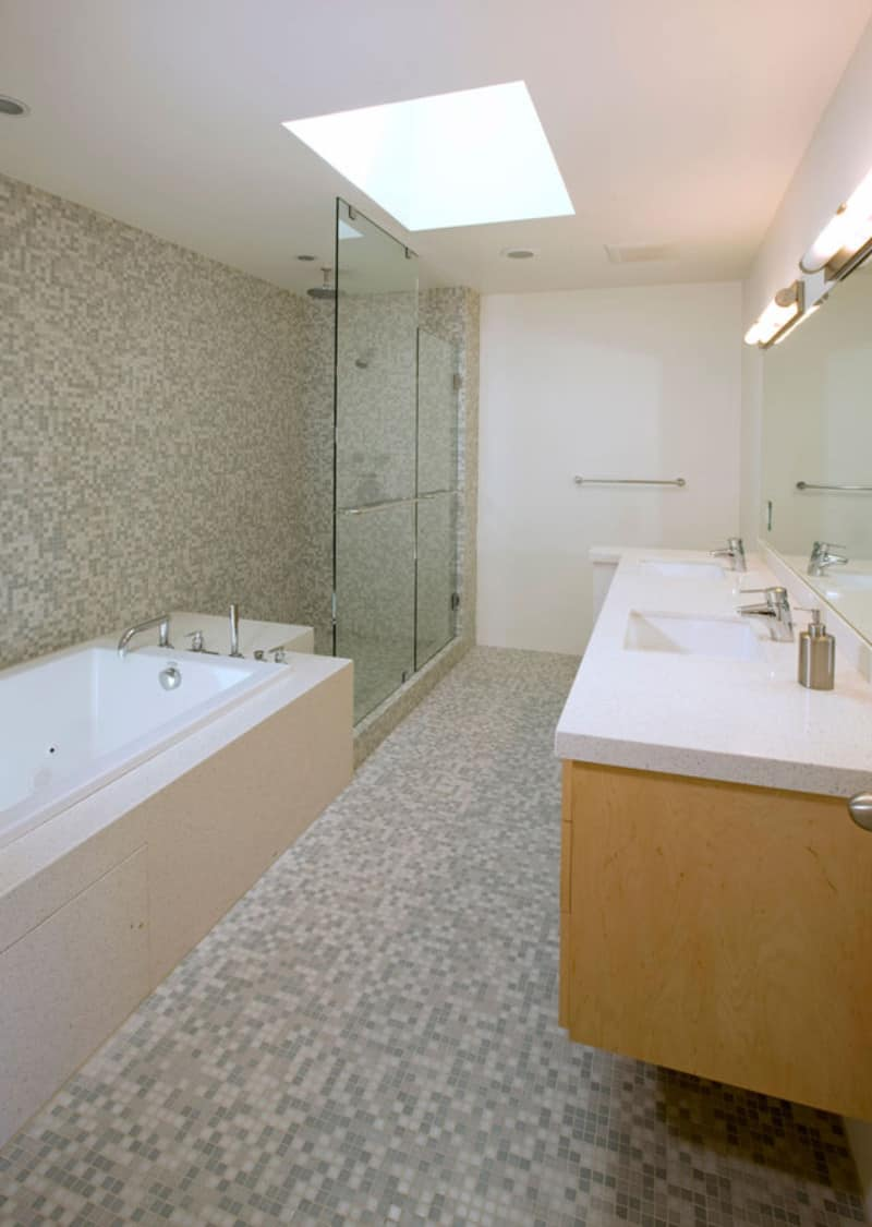 A primary bathroom with stylish tiles floors and walls along with a walk-in shower, a bathtub and a double sink lighted by a skylight.