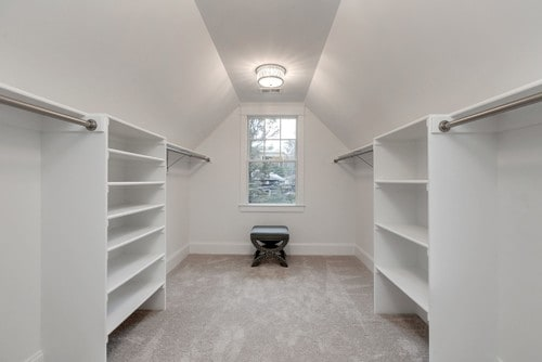 Large white farmhouse closet with carpet flooring.