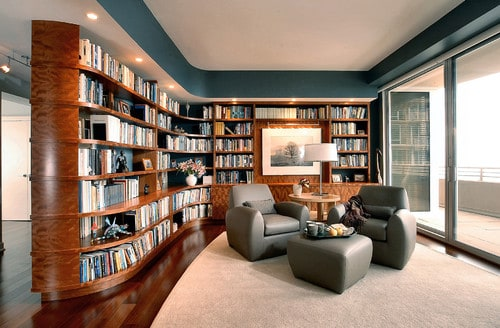 A large, modern reading room with a very idealistic arrangement. The hardwood floor is carpeted while the shelves are built with a unique design.