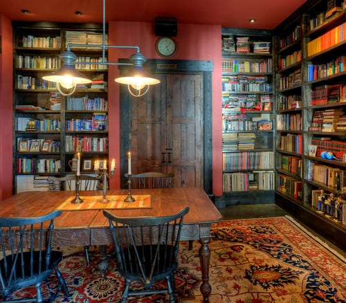 A vintage-looking reading room with red walls and carpeted hardwood floor.
