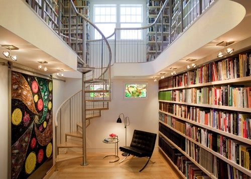 Two-story reading room in a modern style. Aside from the random arrangements of the books, the colorful painting also gives life to its light-colored walls and floor.