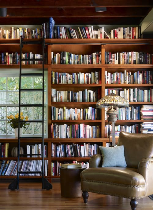 A small reading nook with a big and connected shelf made up of wood.