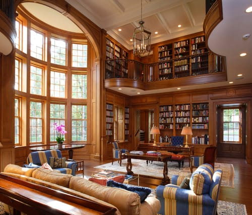 A large living room with a reading nook. The overall finish of the room is indeed extravagant with smooth, industrialized wood as the main medium.
