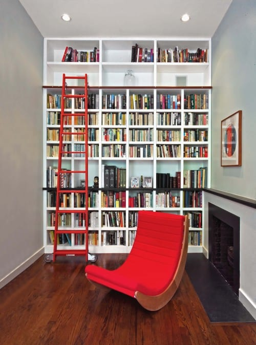 A small reading nook with a hardwood floor and bold red furniture in a cozy fireplace
