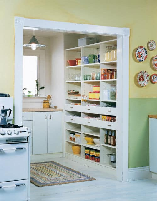 rustic kitchen walk-in pantry with white cabinets and laminated floors