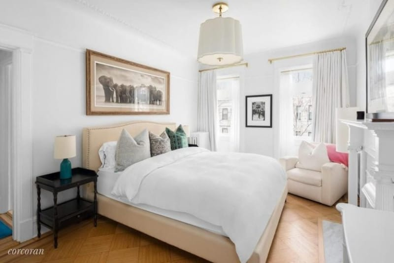John Krasinski and Emily Blunt has a mid-size contemporary bedroom for a guest or two with transitional light wooden floors and elegant pendant light.