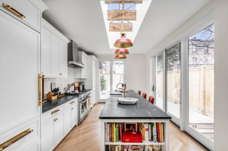 Floor to ceiling glass windows and doors plus a skylight with exposed wood beams where pendant lights are hung bring a lot of light in on this bright white kitchen accented by gold.