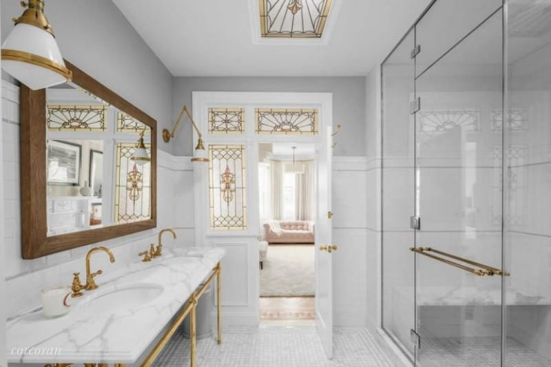 This primary bathroom offers two sinks with marble countertop lighted by wall lights. In front of the sinks is the walk-in shower.