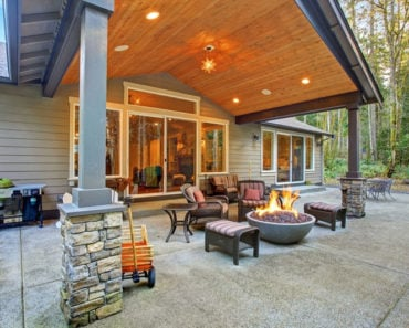 large back yard with grass and covered patio with fire pit