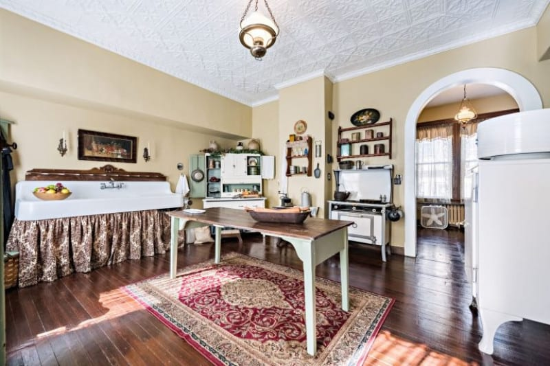 Old-fashioned kitchen with tin ceiling, white countertop, pendant lights and a center wooden table that sits on a red printed rug.