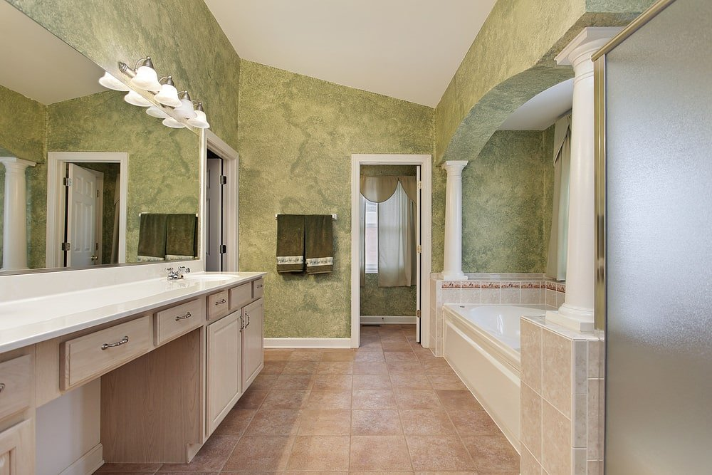 This simple Mediterranean-style primary bathroom is complemented by its cloudy green walls that go well with the white countertop of the wooden two-sink vanity and the two small white pillars that flank the bathtub inlaid with the same beige tiles as the flooring.