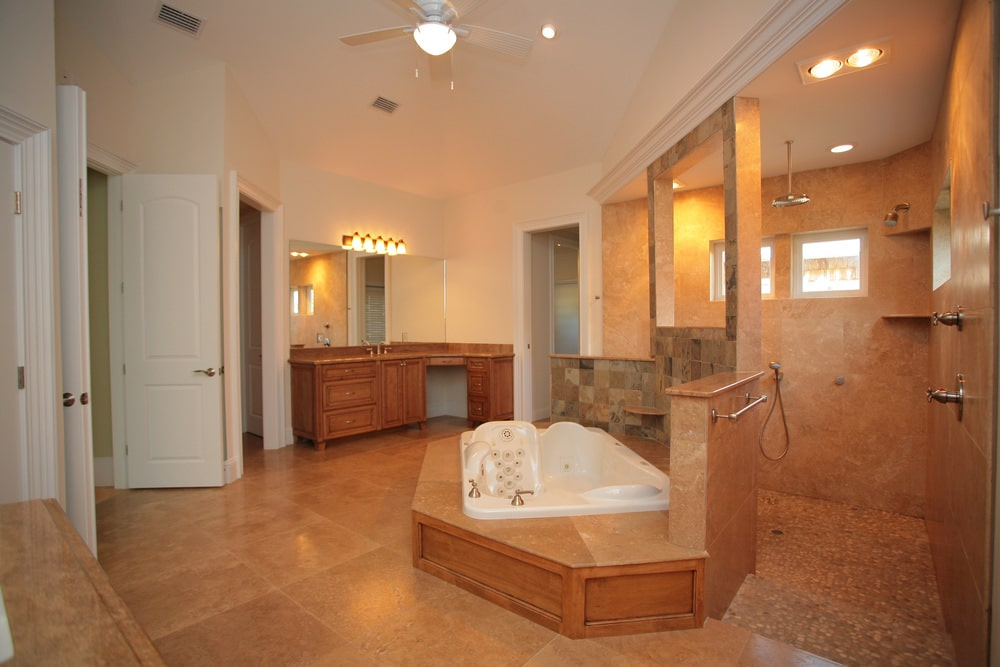 The white luxurious bathtub is housed in a small platform with the same brown tiles as the floor and the same wooden siding as the wooden L-shaped vanity on the far corner. This is topped with a row of wall-mounted lamps that cast of a warm yellow light that matches the recessed lights over the shower area.