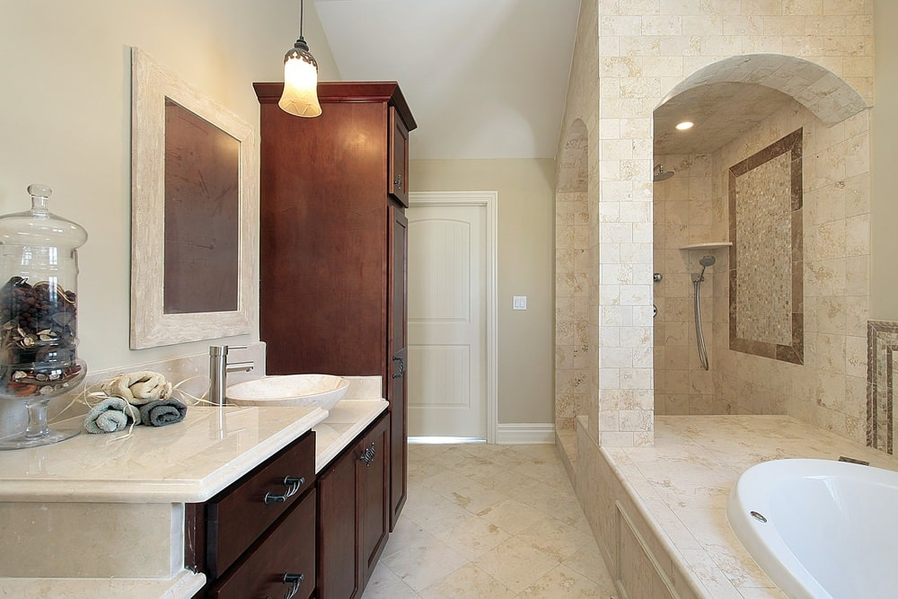 The small floor space is maximized in this Mediterranean-style primary bathroom. The dark wooden vanity and its cabinets and drawers are placed across from the bathtub that is housed with the same beige marble as the floors and the shower area beside it.