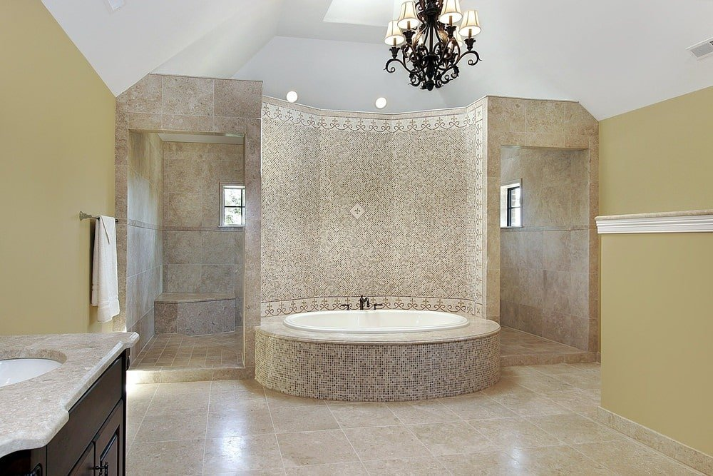 The elliptical white porcelain bathtub is housed with patterned small tiles on its side and its curved wall to provide a complex background for the two flanking entryways into the shower area that has the same beige marble as the flooring.
