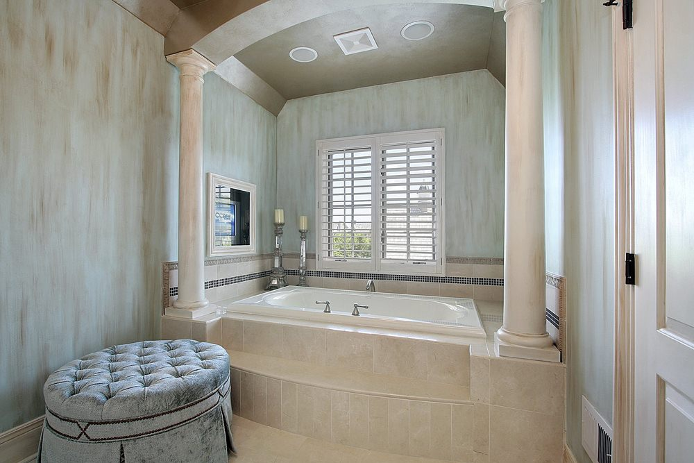 This chic and elegant Mediterranean-style bathroom has a light blue velvet cushioned ottoman that matches with the hue of the walls brightened by the shuttered white windows above the bathtub and contrasted by the dark brown ceiling.